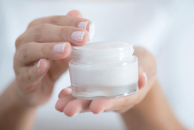 Dettagli di una mano di donna che prende della crema da un vasetto
