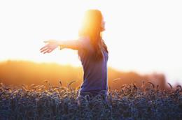 Una ragazza a braccia aperte in un campo