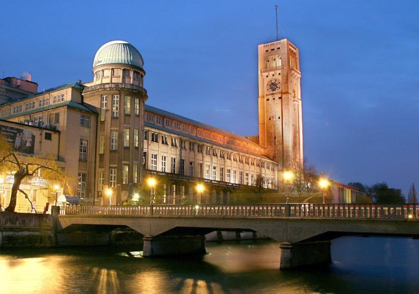 Il Deutsches Museum lungo il fiume Isar illuminato dalle luci della sera.
