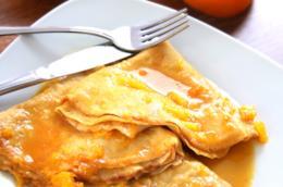 Crêpes con salsa di arancia su piatto quadrato con arance tagliate a metà