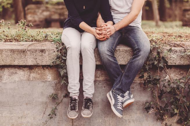 Un ragazzo e una ragazza si tengono per mano seduti su un muretto