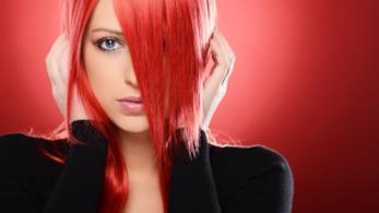 Bella ragazza rossa che tiene le mani sui capelli, altezza orecchie