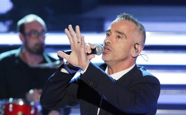 Primo piano di Eros Ramazzotti, in nero, che canta al microfono, con il braccio sinistro sollevato