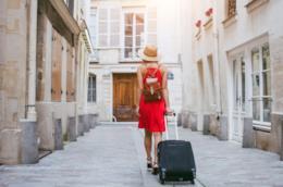 Ragazza di spalle in abito rosso con valigia