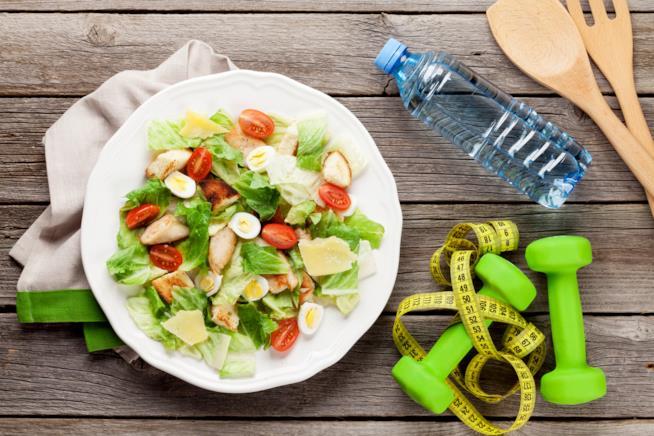 Piatto di insalata su un tavolo insieme a un centimetro e a dei pesetti