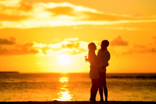 Coppia brinda al tramonto in riva al mare