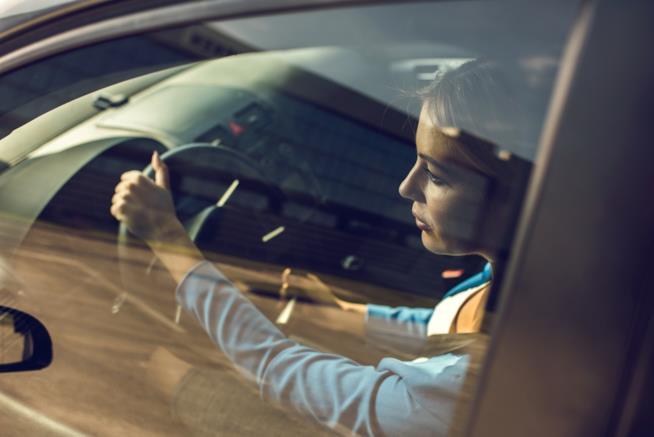 Donna al volante oltre il finestrino