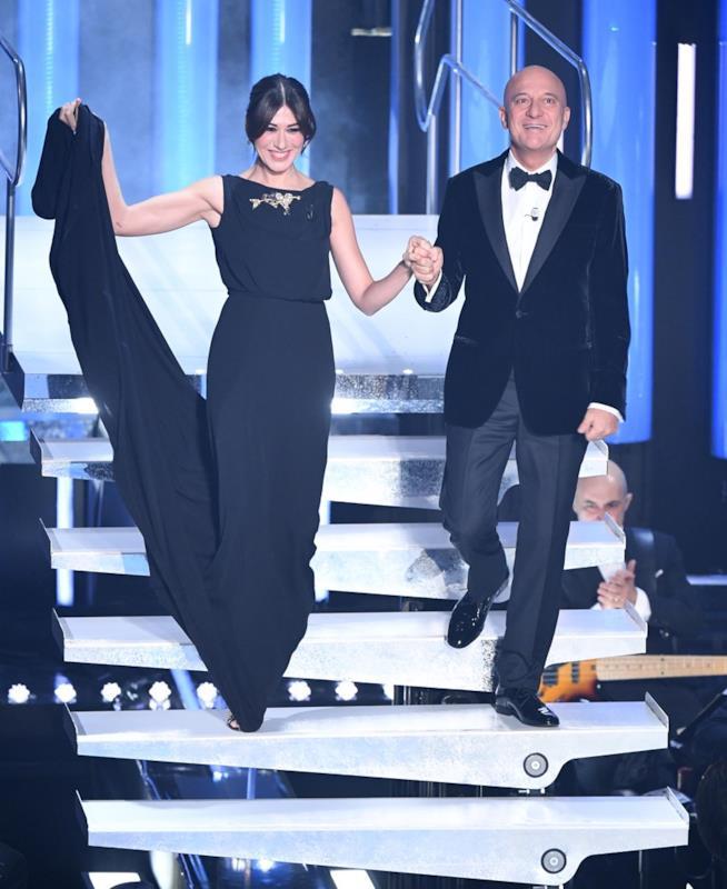 Virginia Raffaele e Claudio Bisio, mano nella mano, in nero, scendono le scale