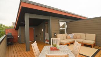 Terrazza con pavimento in legno, sedie e tavolo, due sofà e un piccolo barbeque nell'angolo