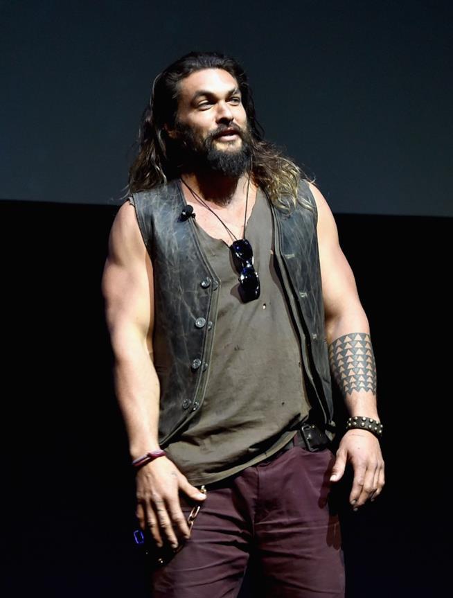 Jason Momoa in piedi, con il tatuaggio sul braccio sinistro in bella vista
