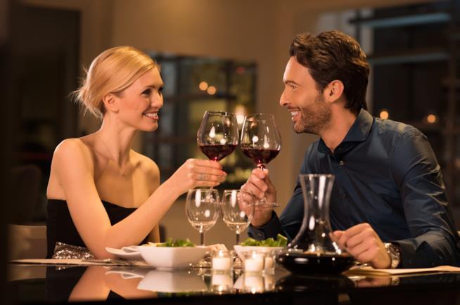 Una coppia brinda seduta a un tavolo
