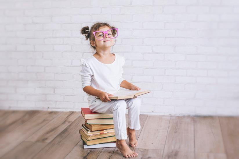 Una bambina seduta su dei libri.