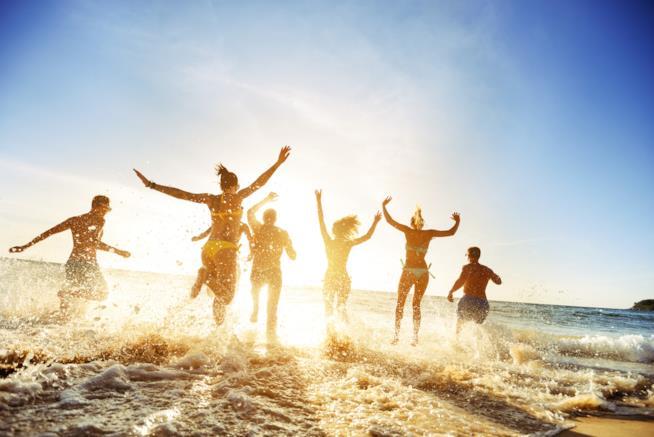 Un gruppo di ragazzi si tuffa in mare felice