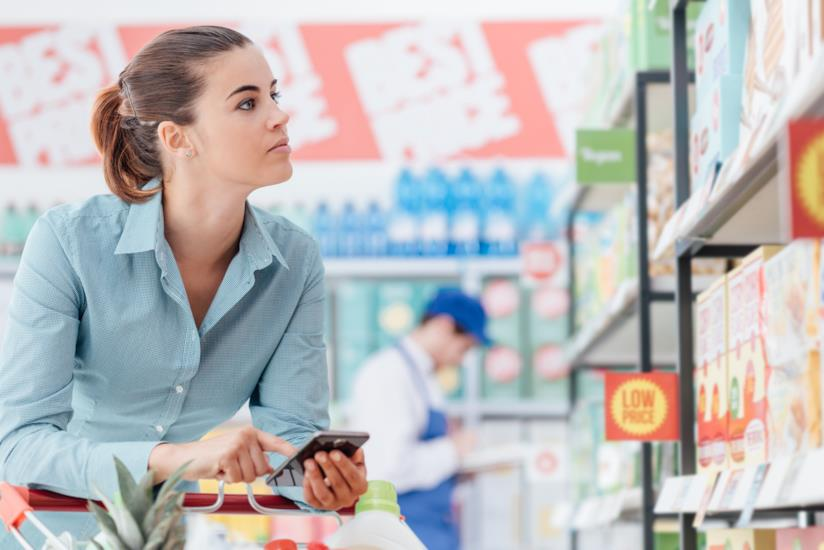 Una donna al supermercato con il telefono in mano.