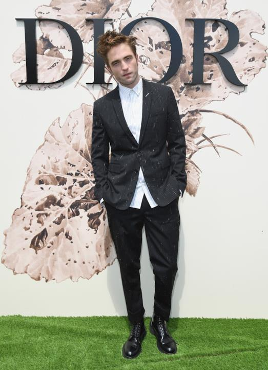 Robert Pattinson posa davanti al logo Dior