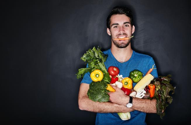 Un ragazzo stringe al petto dei vegetali tenendo una carota in bocca