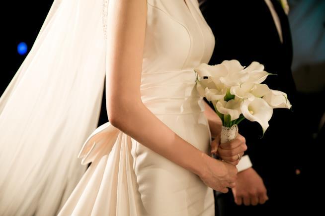 Coppia di sposi con bouquet di calle