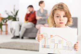 Una bambina tiene in mano il disegno di una casa