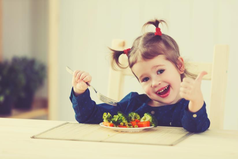 Bambina felice di mangiare le verdure