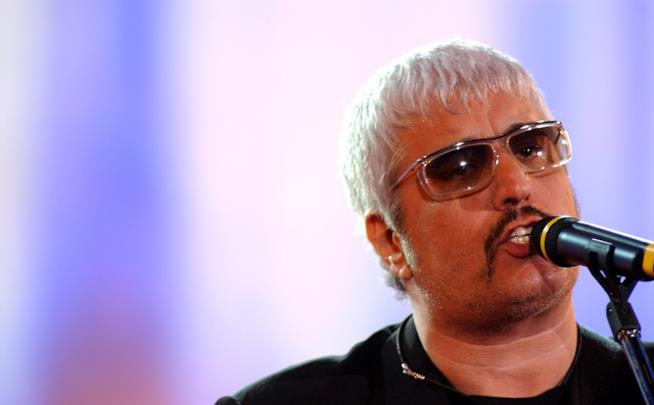 Pino Daniele, davanti al microfono, indossa degli occhiali da sole