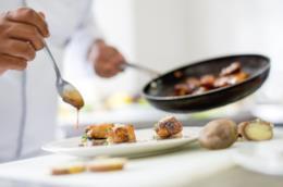 Un cuoco decora il piatto dandogli il tocco finale
