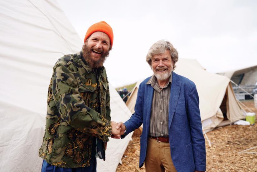 Jovanotti e Messner, sorridenti, si stringono la mano