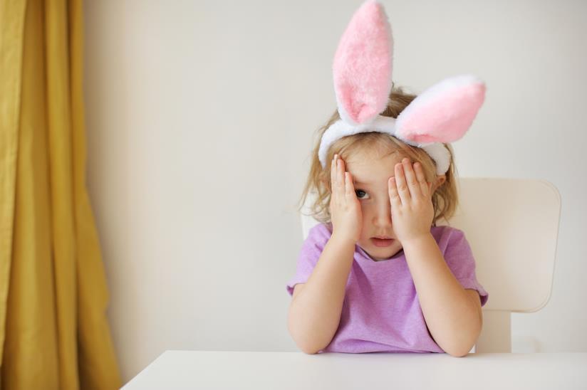 Una bambina che si copre gli occhi.
