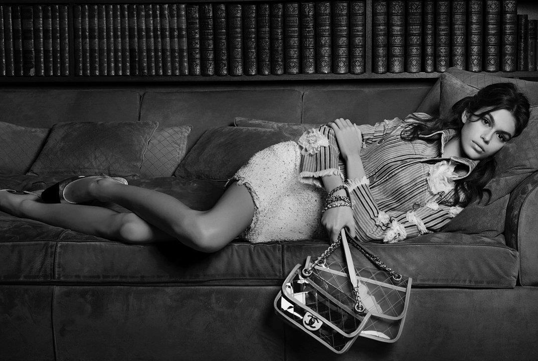 Kaia Gerber sul divano con due borse in mano
