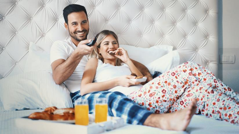 Giovane coppia sdraiata sul letto guarda la televisione mentre fa colazione