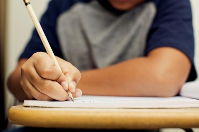 Un bambino scrive su un quaderno