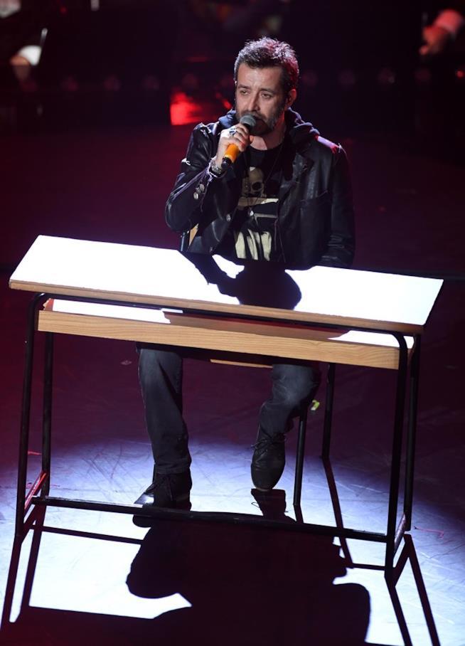Daniele Silvestri, canta al microfono, seduto di fronte a un banco di scuola