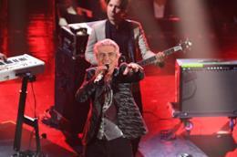 Luciano Ligabue, con una giacca nera, il microfono in mano, sorride, davanti al bassista