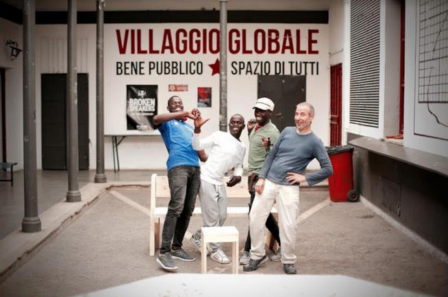 Tre ragazzi e un uomo, in piedi, di fronte alla scritta Villaggio globale