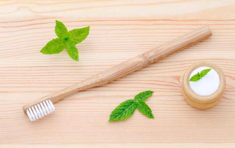 Uno spazzolino di bamboo e un barattolino di dentifricio e menta