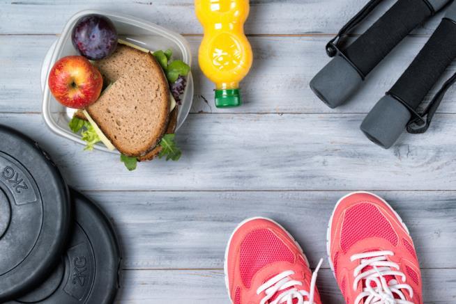 Scarpe da ginnastica, pesi, panino integrale con verdure e bottiglia con succo