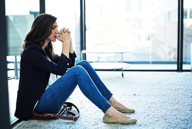 Una donna è seduta a terra con aria avvilita