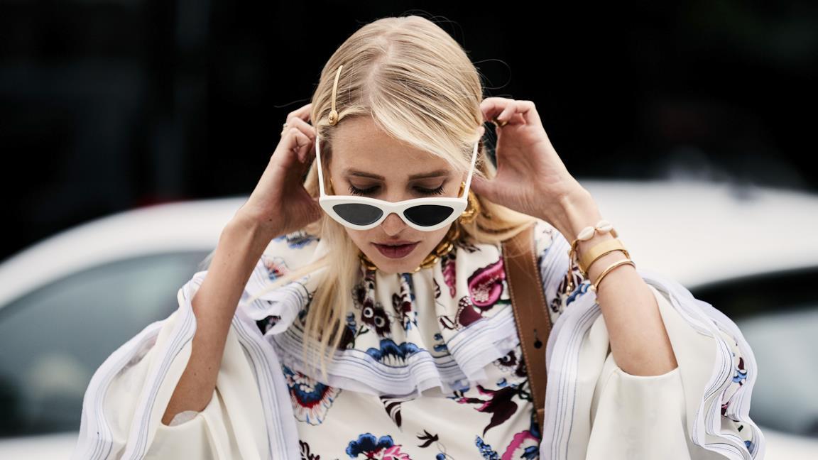 Modella in posa con blusa bianca e occhiali