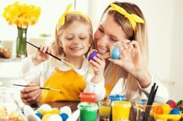 Mamma e figlia che decorano uova pasquali
