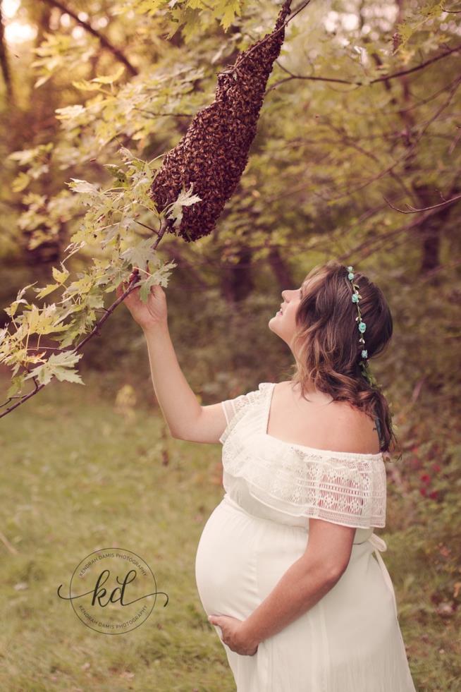 Una donna col pancione vicino ad un ramo coperto di api