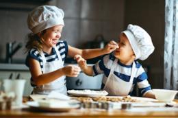 Due bambini cucinano insieme divertendosi