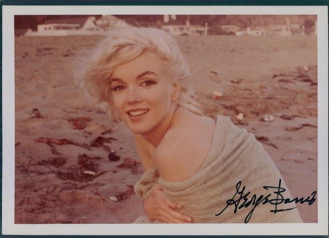 Marilyn Monroe accovacciata in spiaggia avvolta da un asciugamano