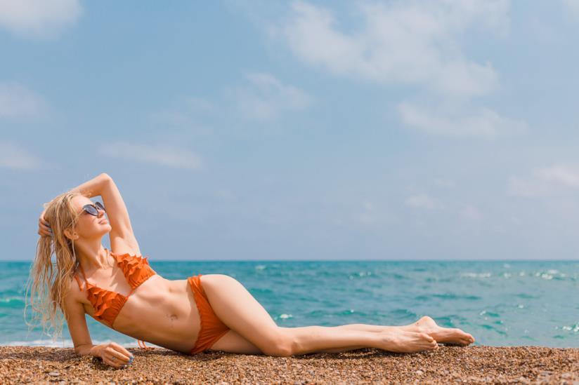 Ragazza con i capelli lunghi e lisci in spiaggia
