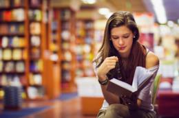 Ragazza legge un libro in biblioteca