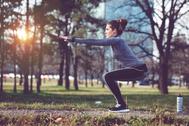 Un'atleta fa squat in un parco