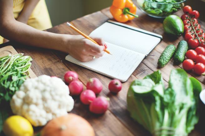 Una donna scrive una ricetta su un taccuino posato su un tavolo con delle verdure