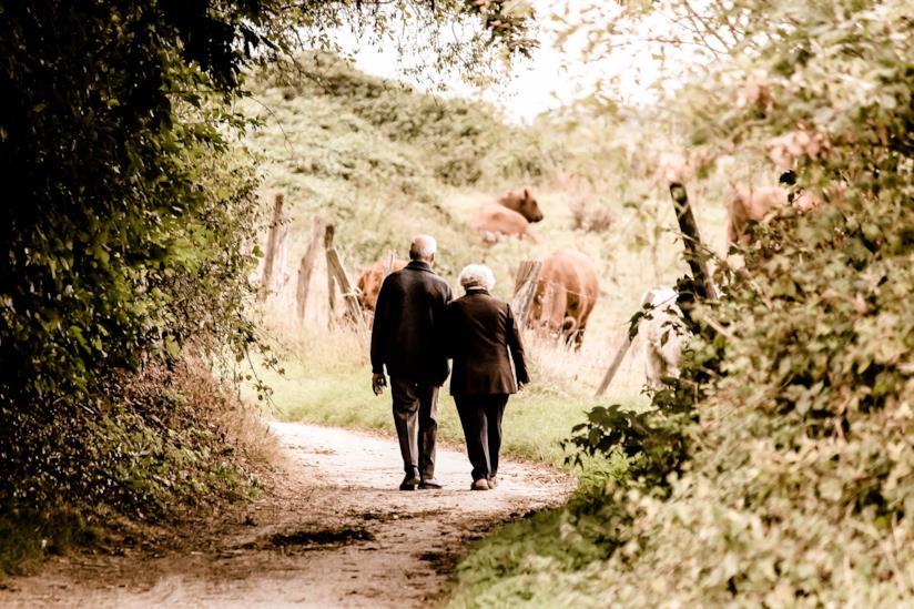 Coppia di anziani passeggia lungo il sentiero di un bosco