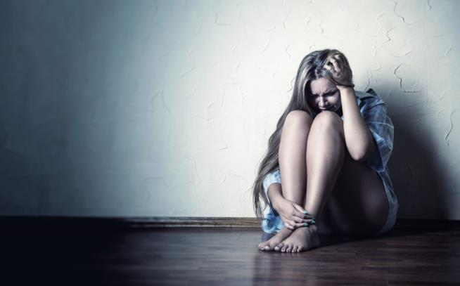 Donna seduta a terra in lacrime
