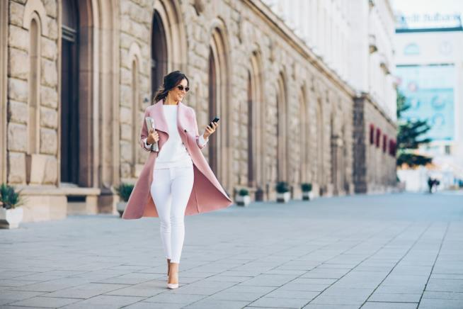 Ragazza in bianco con cappotto rosa passeggia