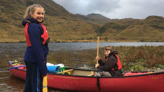 Due dei piccoli della famiglia Cluett in una canoa rossa
