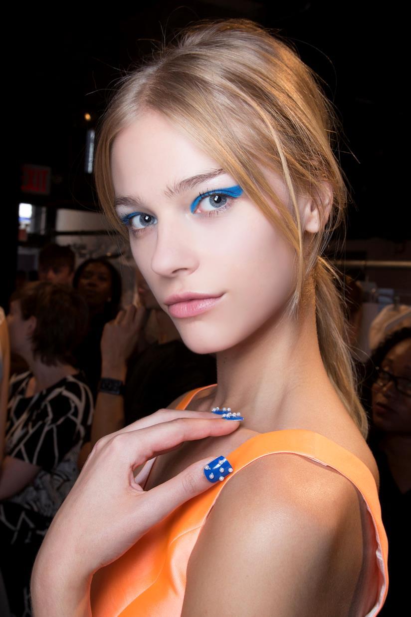 Nail art in gel blu con decorazioni bianche